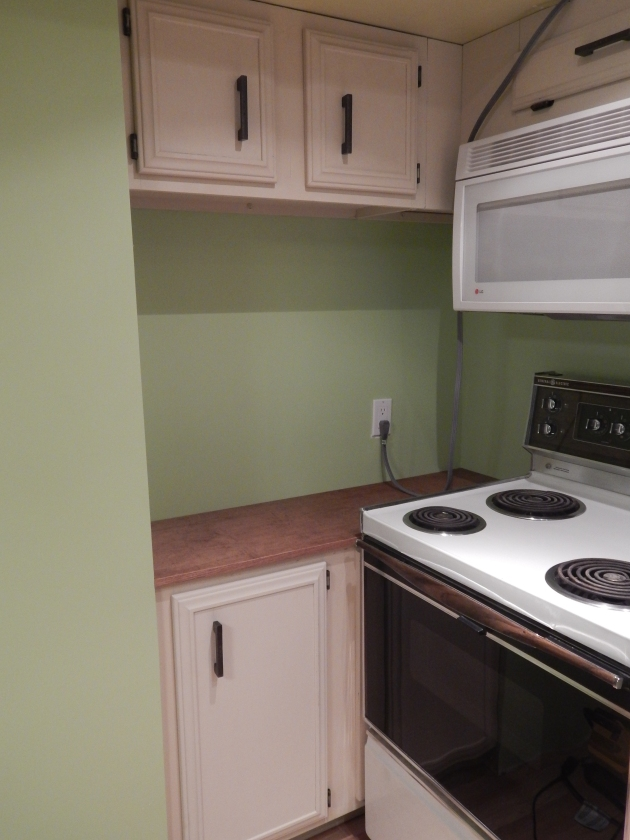 This is actually a great idea for this corner. Instead of wasted space, there is a fake cupboard behind to the side of the stove. The original plan had the stove sitting where the small counter is but we decided it looked disjointed that way.